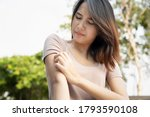 Small photo of Asian woman scratching her arm; concept of dry skin, allergic skin inflammation, body care, fungus infection, eczema, dermatitis, rash, mosquito or insect bite