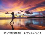 Small photo of Summer travel vacation concept, Traveler asian woman with hat relax and sightseeing on Kata beach at sunset in Phuket, Thailand