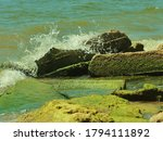 Small photo of Waves crashing on the missy rocks of that lake shore.