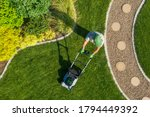 Small photo of Caucasian Gardener Mowing Backyard Garden Grass Using Cordless Electric Grass Mower. Aerial View. Gardening and Landscaping Industry.