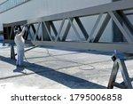 Powder coating of metal parts.  Hand holding powder coating sprayer