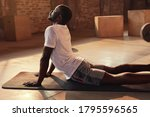 Small photo of Body stretch. Fit man stretching back, doing yoga workout at gym. Black male athlete doing back extension stretch exercise lying on mat indoors