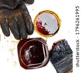 Small photo of Tar in a plastic jar, brash and glove isolated on white background.