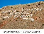 Worlds Largest Mineral Hot Spring written on a mountainside in Hot Springs State Park located in Thermopolis, Wyoming