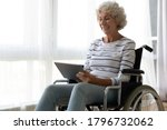 Small photo of Happy old mature disabled woman sitting in invalid carriage, using computer tablet, enjoying communicating with friends online, watching funny movie or TV series indoors, handicapped people lifestyle.