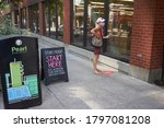 Small photo of Portland, OR, USA - Aug 16, 2020: A masked shopper waits outside the Powell's book store in the Pearl District of Portland, Oregon, for store pickup, during a pandemic summer.