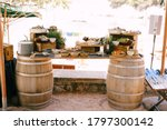 Small photo of An impromptu table of two wine barrels and a wooden bar with delicacies and flowers.