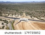 Construction of a bridge and underpass on a busy road in the desert - stock photo