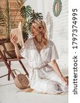Small photo of Fashionable happy smiling woman wearing white crochet jumpsuit, holding straw hat, with wicker bag, posing in stylish boho interior. Summer fashion conception
