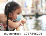 Small photo of Asian child or kid girl wear N95 blue face mask to close mouth nose with cold cough sick and sneeze flu to sit chin on arm on bamboo rail and pond for protect coronavirus or dust and sad absent-minded