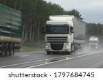Small photo of Semi trucks lorry convoy move on suburban wet asphalted highway front view on cloudy summer day, safety drive overtake on rain slippery road on green forest background