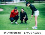 Small photo of Golf putting lesson, two young female golfers practicing putting with golf instructor