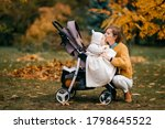 Handsome little baby with big blue eyes, short red hair, pump lips in a stroller outside in the fall with its nice happy mum