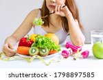 Small photo of Unhappy young Asian woman bored emotion on dieting time and refuse eating fresh green vegetables in fork on dining room at home, gird dislike taste of vegetable. Healthy food concept