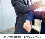 Small photo of Elbow bump. Safety greetings. Businessman and business woman use elbow to bump into greeting. New way to greet, instead of shaking hands to avoid the spread of coronavirus.