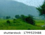 Small photo of Water droplets on glass and Monsoon Landscape in the background at Purandar near Pune India. Monsoon is the annual rainy season in India from June to September.