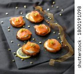 Small photo of cottage cheese and smoked salmon toasts with lemon zest on a slate, black background