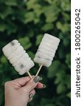 Small photo of Two Fruit white ice cream on a stick in the girl's hand. The ice cream shows the blue berries of blueberries. Green background. Homemade ice cream. Cold dessert. Vegetarian ice cream.