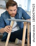 Man Repairing A Wooden Table