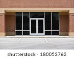 A new unoccupied generic store front, business or professional office space in a contemporary strip mall. Red brick with dark tinted windows in brushed aluminum frames and a double door.