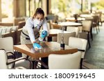 Young Waitress Disinfecting...