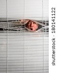 Small photo of Agoraphobia. A man looking through a window blind with facial expressions.