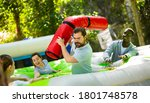 Small photo of Adults having fun on inflatable amusement playground. Expressive bearded guy fighting off his friends with inflatable log while they trying to filch toy chickens