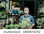 Small photo of Small business and start of working day. Man in protective mask takes out box of plants outside in front of flower shop