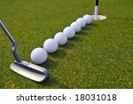 putting golf balls in line to cup - stock photo