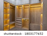Small photo of Interior design decor furnishing of luxury show home bedroom showing walk in wooden wardrobe closet furniture