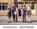 Small photo of Middle school students standing in the schoolyard. Ready to learn and comprehend new things, get high marks. Holding textbooks, a laptop, and school bags on their backs. Warm, sunny evening.