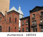 This is a very beautiful group of brownstones with a church in the background in Manhattan. 
