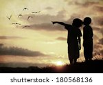 Kids silhouette looking at birds on the sky in air - stock photo