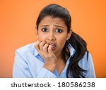 Small photo of Closeup portrait of young unhappy woman, biting her nails looking at you with craving for something, anxious, worried isolated on orange, red background. Negative emotions, facial expression, feelings