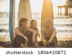 Three Surfers Relaxing On The...