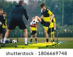 Small photo of Teenagers on soccer training camp. Boys practice football with young coaches. Junior level athletes improving soccer skills on outdoor training. Player kick soccer ball to coach and ladder skipping