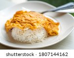 Small photo of Easy Thai food menu, Thai omelette over rice or Kai Jeaw Rad Kow. Close up Thai omelette over white rice in white plate on table.