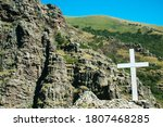 White Cross In Mountains On Hill