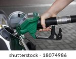 Hand holding green fuel pump refuelling a car - stock photo
