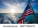 American Flag And Sunrise Over...