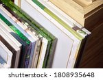 Small photo of Canvas prints, stack of colorful photos with gallery wrapping method of canvas stretching on wooden stretcher bars. Samples of stretched photo canvases. Staple mount, back view