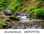 mountain river with stones and moss in the forest near the mountain slope  - stock photo