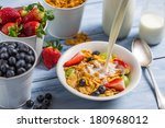 Pouring milk into cornflakes with fruits - stock photo