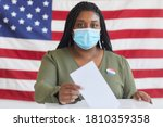 Small photo of Portrait of young African-American woman wearing mask putting vote bulletin in ballot box and looking at camera while standing against American flag on election day, copy space