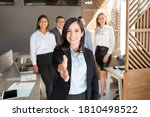 Small photo of Caucasian businesswoman extending her hand for a handshake with colleagues standing in background
