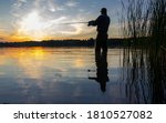 Angler catching the fish in the lake during sunset