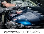 Small photo of Man with orbital polisher in repair shop polishing car. Car detailing