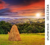 a pair of haystacks and a tree on a green meadow at the foot of the mountain at sunset - stock photo