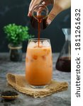 Small photo of A hand pouring black aroma tea into a glass of traditional Thai iced tea with milk latte.It is a mix of spices, sugar, sweetened condensed & evaporated milk sold on many streets of Thailand