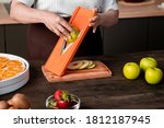 Small photo of Close-up of unrecognizable woman using mandoline slicer for cutting apple while preparing fruits for dehydration at home